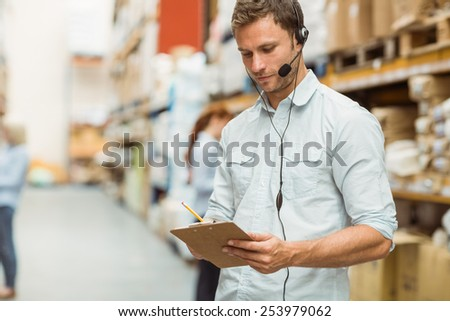 Warehouse manager wearing headset writing on clipboard in a large warehouse - stock photo