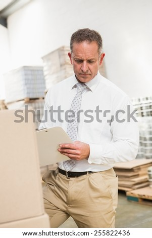 Warehouse manager writing on clipboard in warehouse