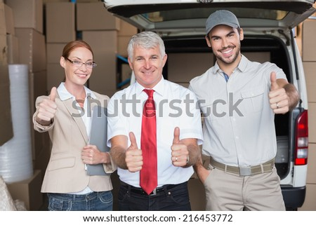 Warehouse managers and delivery driver smiling at camera in a large warehouse - stock photo