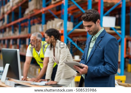 Warehouse managers and worker working together in warehouse office