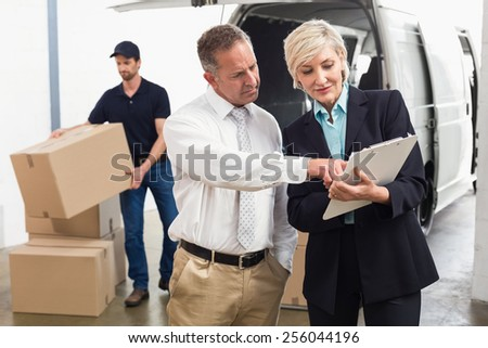 Warehouse managers checking their list in a large warehouse - stock photo