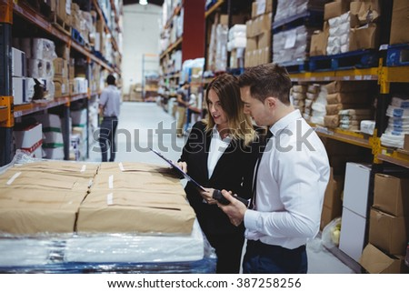 Warehouse managers looking at clipboard in warehouse - stock photo