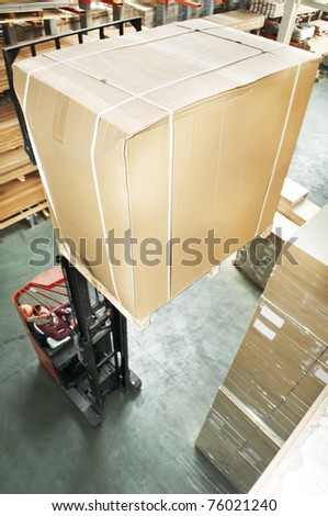 warehouse stacker forklift lifting large cardboard box - stock photo