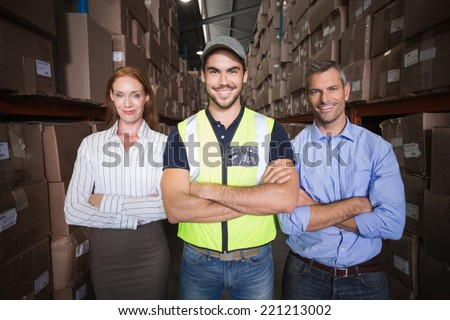 Warehouse team smiling at camera showing thumbs up in a large warehouse - stock photo