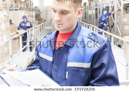 warehouse three workers one man and two woman in a special blue uniform is recording and accounting of contents in cardboard boxes in stock No faces idea account statistics rediscount cargo arrival - stock photo