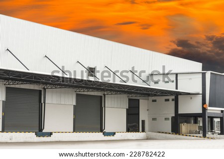 Warehouse with color orange sky - stock photo