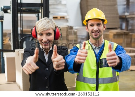 Warehouse worker and his manager giving thumbs up in a large warehouse - stock photo