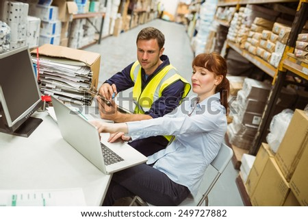 Warehouse worker and manager looking at laptop in a large warehouse