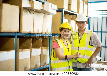 Warehouse worker checking stock products for shipping to customer. - stock photo