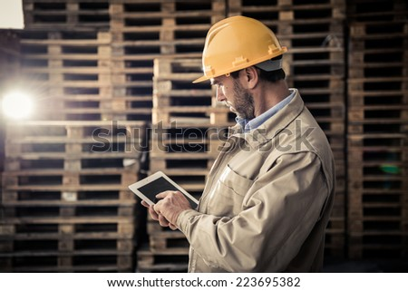 Warehouse worker doing a checklist using a PC tablet - stock photo