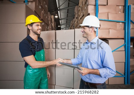 Warehouse worker loading up a pallet with manager in a large warehouse - stock photo