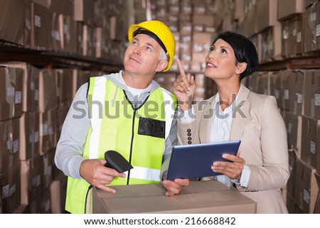 Warehouse worker scanning box with manager in a large warehouse - stock photo