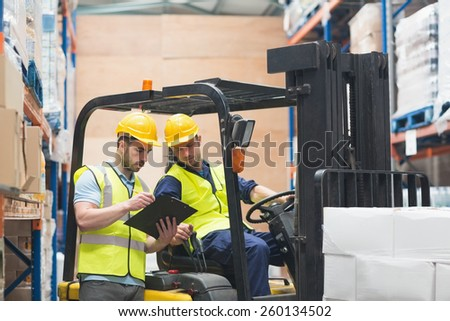 Warehouse worker talking with forklift driver in warehouse - stock photo