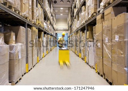 Warehouse worker with a yellow hand pallet truck - stock photo