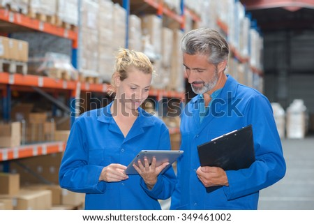 Warehouse workers looking at tablet - stock photo