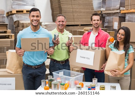 Warehouse workers packing up donation boxes in a large warehouse - stock photo