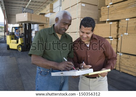 Warehouse workers stocktaking in timber factory - stock photo