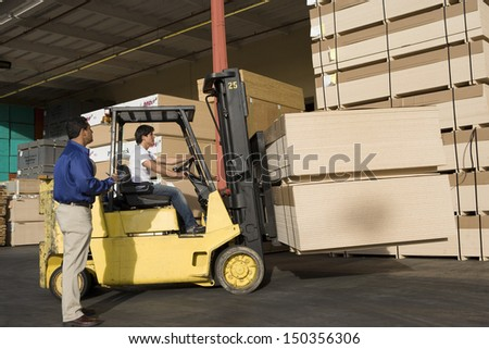 Warehouseman and forklift truck driver working in timber factory - stock photo
