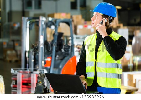 Warehouseman with protective vest, scanner and laptop in warehouse at freight forwarding company using a mobile phone - stock photo