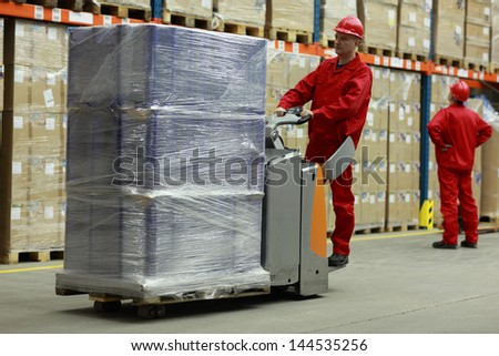 Warehousing - Two workers in uniforms and safety helmets working in storehouse - stock photo