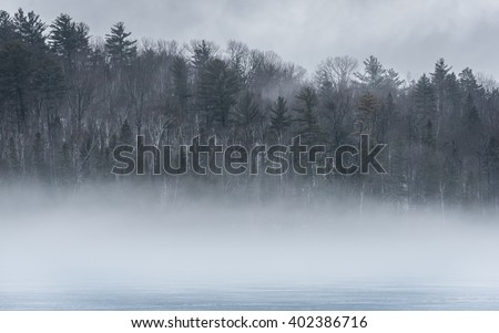 Warm air, cold layers, pale waterfront deciduous Eastern Ontario forest on an early gray day of melting Ice & spring corn snow on thawing Ontario lake.  - stock photo