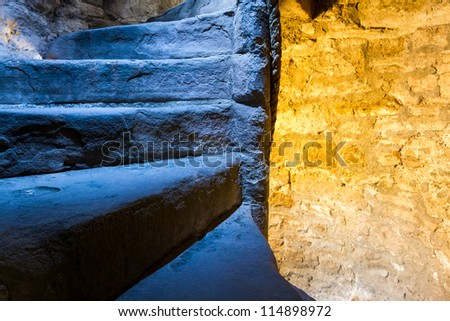Warm and cold light in stone staircase - stock photo