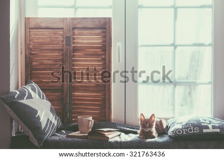 Warm and cozy window seat with cushions and a opened book, light through vintage shutters, rustic style home decor. - stock photo