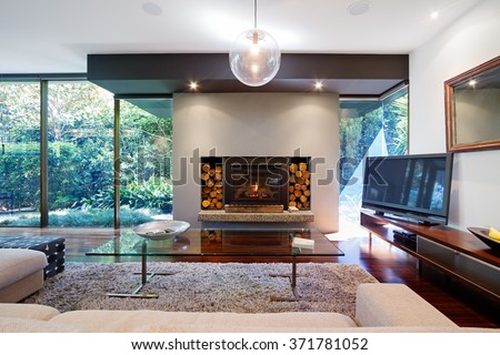 Warm Australian living room with fireplace in contemporary luxury home - stock photo