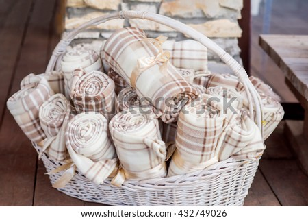 warm beige blankets in a big basket on an open air wedding ceremony