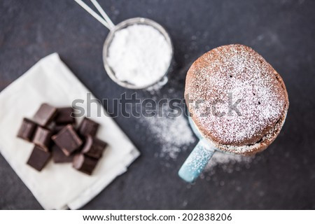 Warm chocolate cake in a mug sprinkled with icing sugar and chocolate chunks