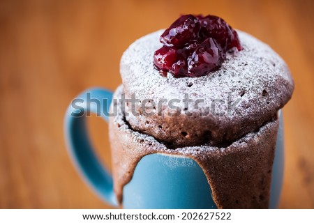 Warm chocolate cake in a mug sprinkled with icing sugar and fresh cherry jam on top
