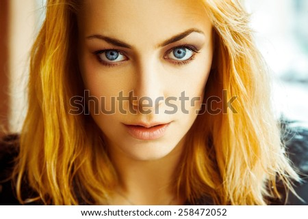Warm close up portrait of gorgeous and serious  adult girl with blue eyes. Horizontal color photo - stock photo