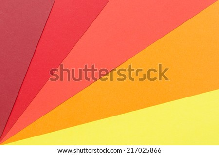 warm-colored construction paper sheets arranged diagonally - stock photo