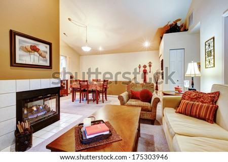 Warm colors living room with fireplace well matched with ivory dining area and cherry dining table set