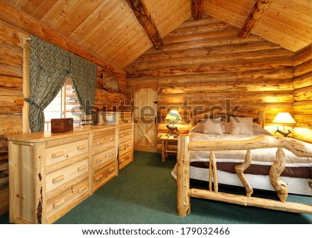 Warm cozy bedroom with rustic bed, nightstand and dresser. Green carpet floor and curtains. Log cabin house interior