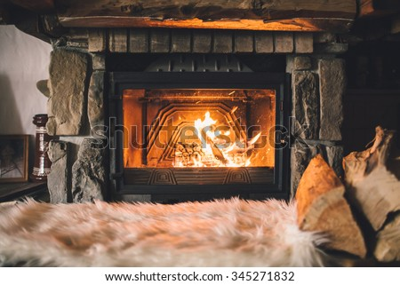 Warm cozy fireplace with real wood burning in it. Cozy winter concept. Christmas and travel background with space for your text. - stock photo