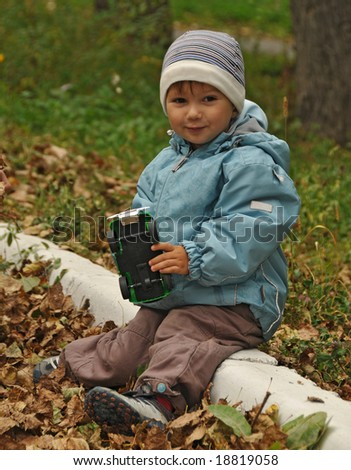 warm dressed boy playing in the fall park - stock photo