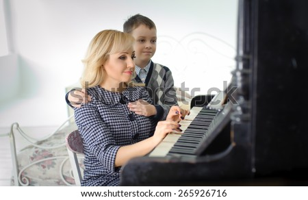 warm family portrait of mother and son near the piano - stock photo