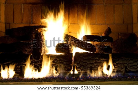 warm fireplace with a fire started - stock photo