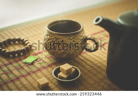 Warm green tea in a traditional cup with a Buddhist bracelet  - stock photo
