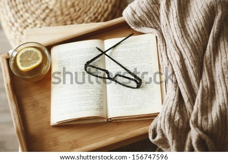 Warm knitted sweater and a book on a wooden tray - stock photo