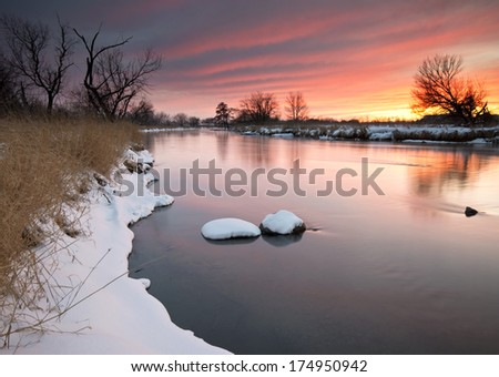 Warm light from a dramatic winter sunset is reflected in the placid surface of the DuPage River at the end of a frigid February day. - stock photo