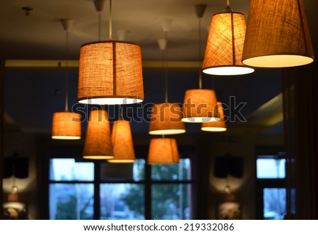 Warm lighting coming out from beautiful lamps on ceiling , against cold lighting from window in a winter day , while taking a hot cup of coffee in a trendy cafe with nice environment - stock photo