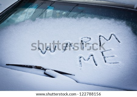 Warm me written in snow on car windscreen below windscreen wiper - stock photo