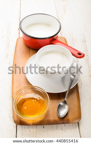 warm milk in a cup and a bowl with sweet honey - stock photo
