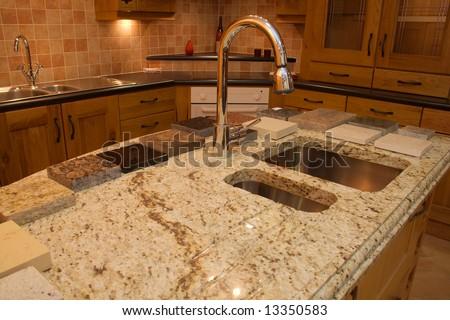 Warm Modern contemporary kitchen showing granite worktop  in showroom - stock photo