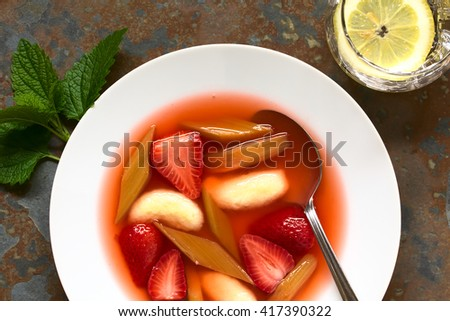 Warm or cold fruit soup made of strawberry, rhubarb and semolina dumplings served in soup plate with spoon, photographed overhead on slate with natural light
