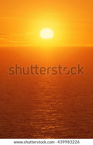 Warm orange sun over open ocean with ripples and light clouds in the sky. Enhanced orange color - stock photo