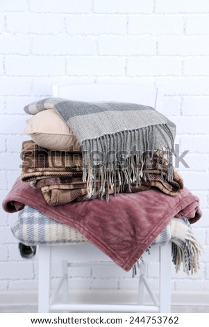 Warm plaids and pillow on white brick wall background - stock photo