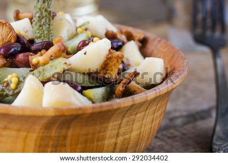 Warm salad from potato and mushrooms with pickles and beans - stock photo